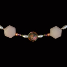 A vintage glass bead is featured in this circarine necklace of rose quartz, pearl, bronze and glass beads.